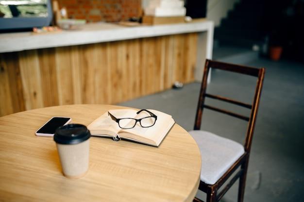 Livre ouvert, tasse de café et verres sur la table au café étudiant