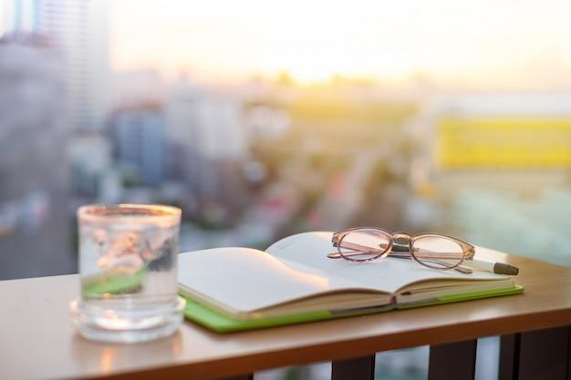 Livre ouvert avec un verre en verre, un stylo et un verre d'eau glacée glacé posés sur wood desktop