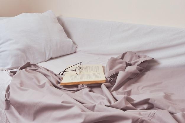 Livre ouvert et verres sur le lit