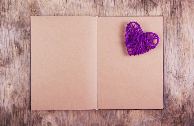 Un livre avec des pages blanches et un fond en bois de coeur en osier.