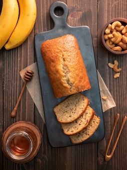 Livre de pain aux bananes maison tranchée avec noix de cajou et miel sur une table en bois.