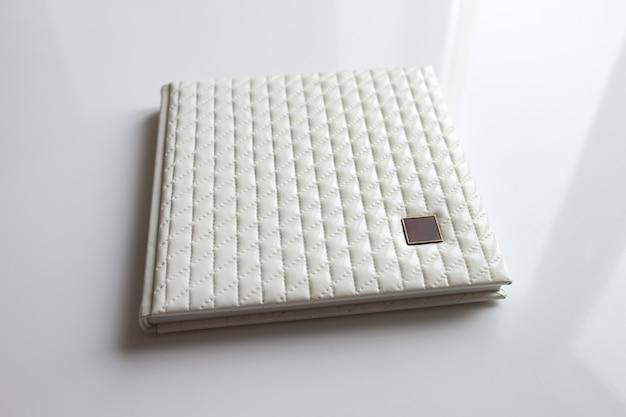 Livre photo avec une couverture en cuir véritable dans la boîte. couleur blanche avec estampage décoratif .focus doux.