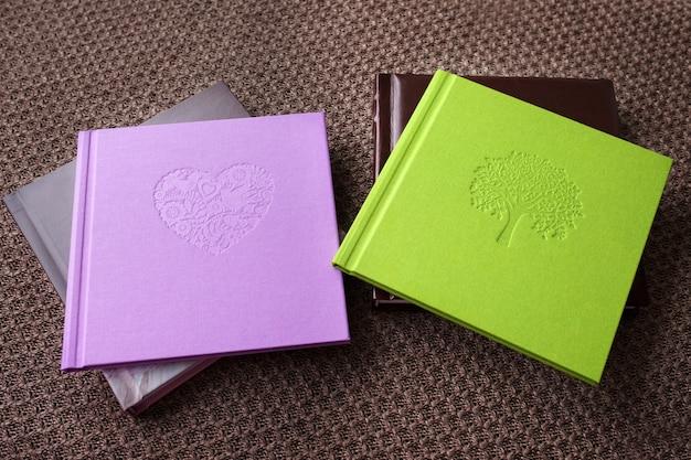 Livre photo avec couverture textile. couleurs violettes et vertes avec estampage décoratif.