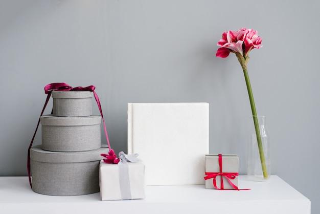 Livre photo entouré de coffrets cadeaux, cadeau et fleur dans un vase sur mur gris