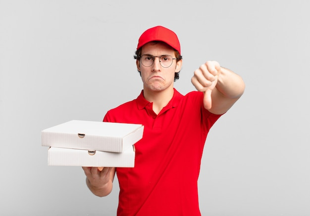Livre de pizza garçon se sentant fâché, en colère, agacé, déçu ou mécontent, montrant les pouces vers le bas avec un regard sérieux