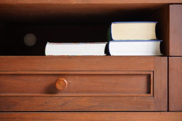 Livre de poche dans une étagère en bois avec fond sombre vide vide