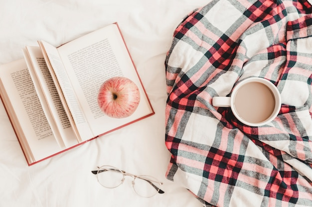 Livre avec pomme sur la boisson chaude dans un plaid et des lunettes