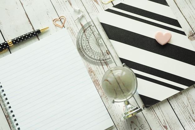 Livre de printemps, cahier noir et blanc, stylo, trombones et globe en verre