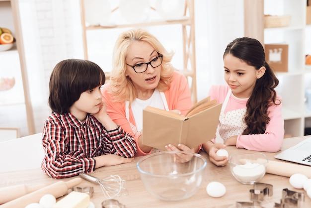 Livre de recettes de lecture de grand-mère avec petits-enfants
