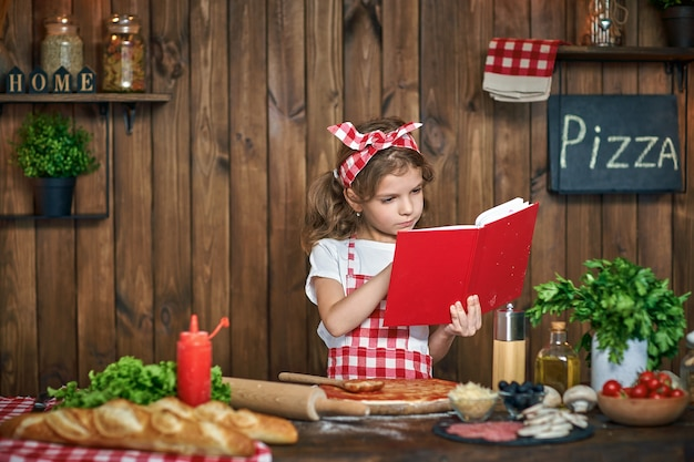 Livre de recettes de lecture jolie fille en tablier à carreaux