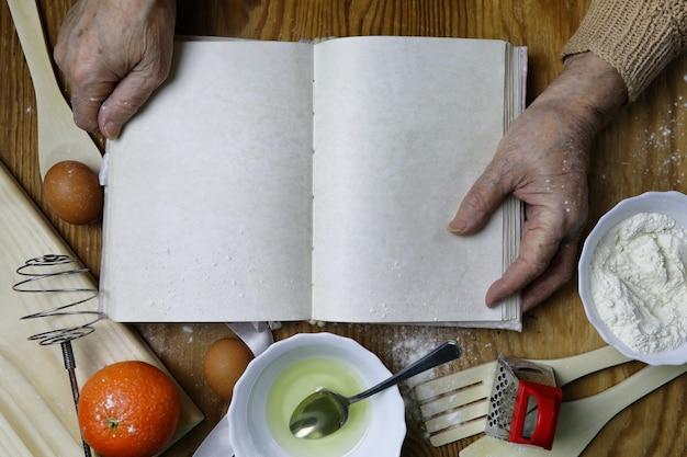 Livre de recettes ouvert entre les mains d'une femme âgée devant une table avec des ustensiles