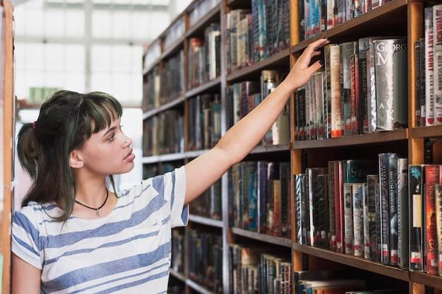 Livre de recherche d'écolière dans la bibliothèque