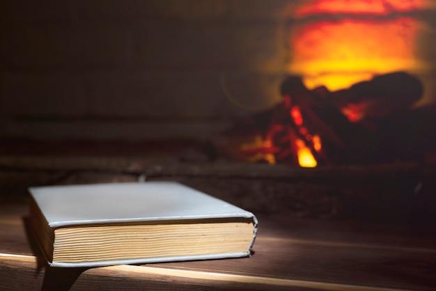 Un livre relié se trouve sur un bois près d'une cheminée en feu