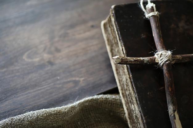 Livre religieux antique et croix en bois sur le fond d'un bois et d'une toile de jute