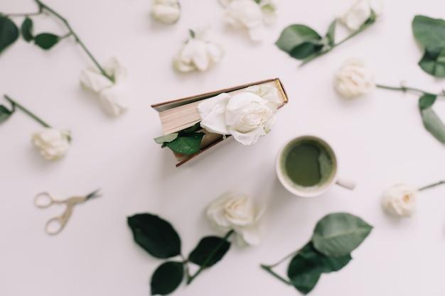 Un livre avec des roses blanches et une tasse de thé vert sur la vue de dessus blanc