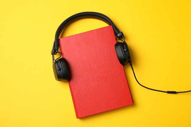 Livre rouge avec un casque sur fond jaune, vue de dessus
