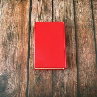 Livre rouge sur fond de bois, vue de dessus, gros plan