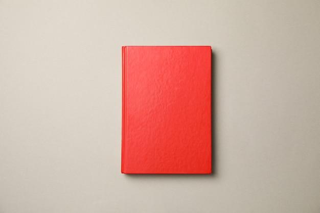 Livre rouge sur fond gris, vue de dessus et espace copie