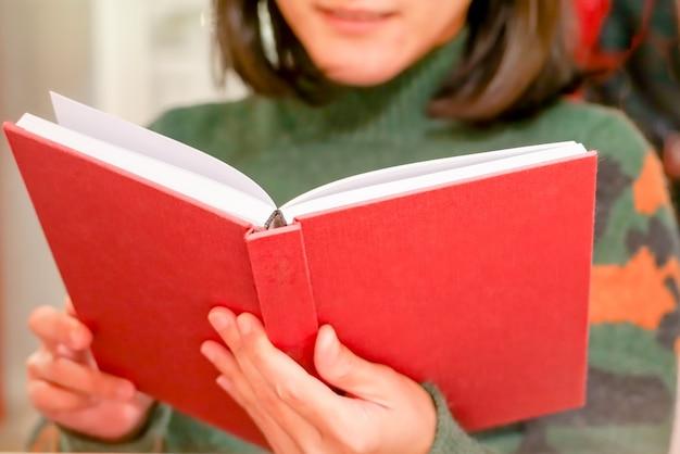 Le livre rouge ouvert tient / lit sur la main des femmes à la maison