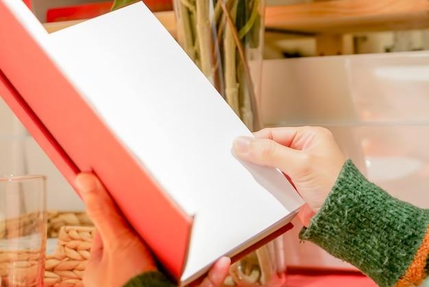 Le livre rouge ouvert et vide lit sur la main des femmes