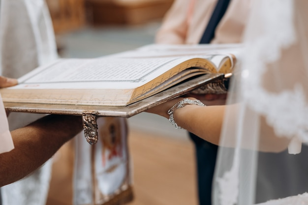 Livre sacré de la bible sur les mains de la mariée sur le rituel du mariage sacramentel à l'église