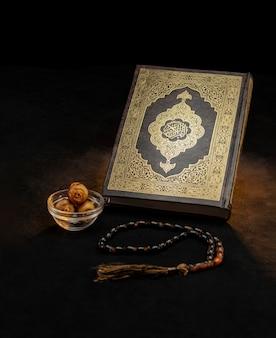 Livre sacré du coran avec chapelet et dates