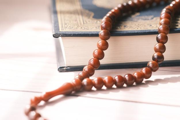 Livre saint coran et chapelet sur table close up