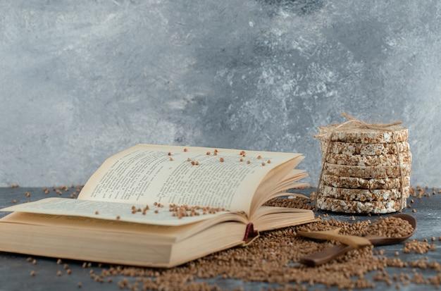 Livre, sarrasin cru et pain croustillant sur une surface en marbre