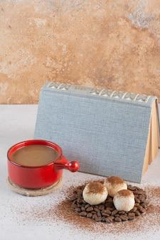 Un livre avec une savoureuse tasse de café aromatique sur fond blanc. photo de haute qualité