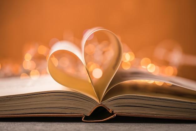Livre avec le symbole de l'amour sur fond rouge, forme de coeur du livre papier.