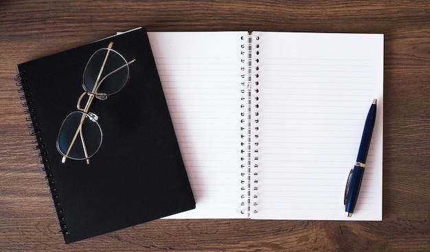 Livre sur une table en bois avec des lunettes et un stylo