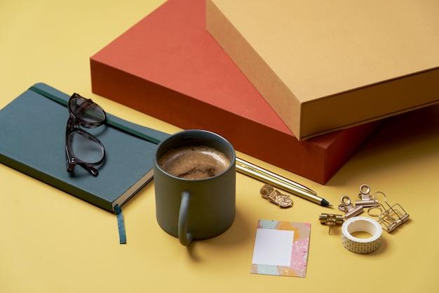 Livre, tasse à café, lunettes de lecture, stylo et crayons sur jaune.