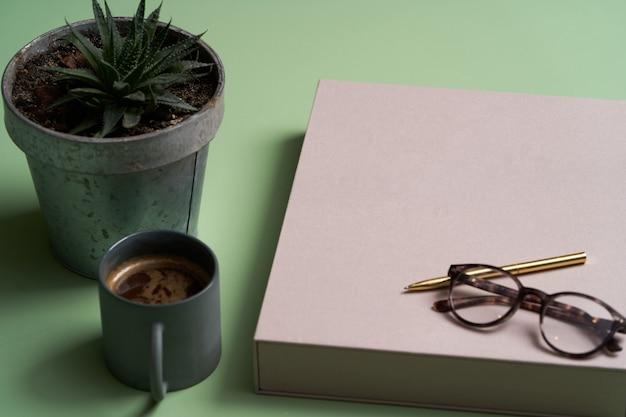 Livre, tasse à café, lunettes de lecture, stylo et crayons sur vert