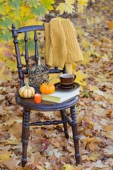 Un livre, une tasse, deux citrouilles orange, une vieille cage en bronze, une bougie orange, un pull jaune tricoté