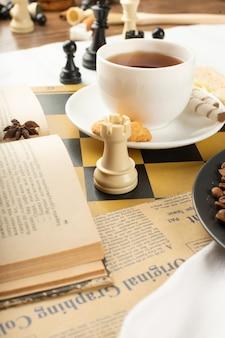 Un livre, une tasse de thé et une tour d'échecs