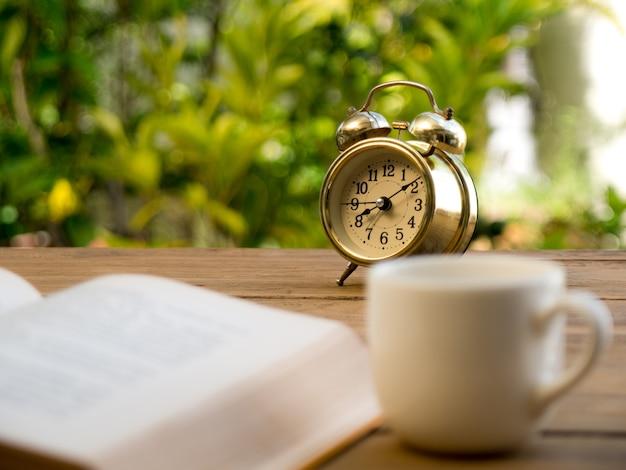 Livre de texte avec réveil vintage et tasse à café blanche sur la table en bois.