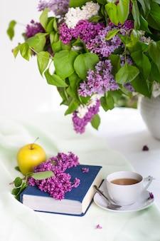 Livre et thé et un grand bouquet de fleurs lilas