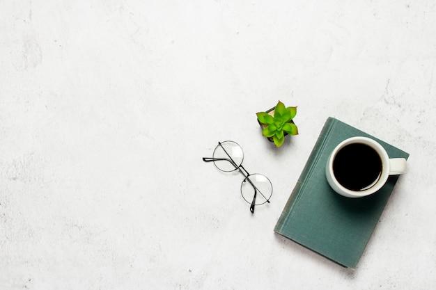 Livre, verres à verres ronds, une tasse de café et une fleur d'intérieur sur fond clair.