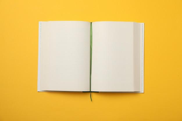 Livre vide ouvert sur l'espace jaune, espace pour le texte