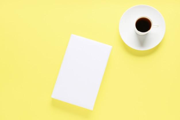 Livre vierge et tasse de café sur fond de couleur