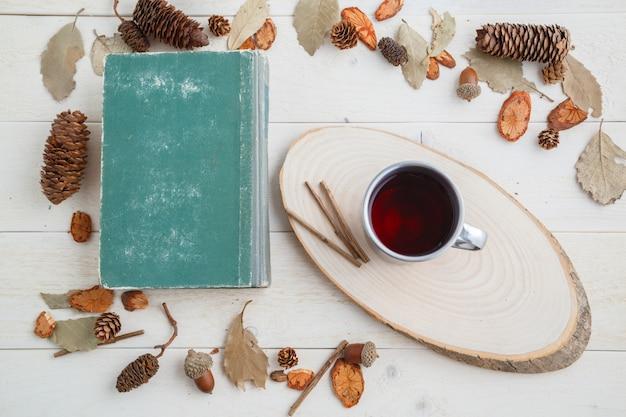 Livre vintage et boire dans une tasse rétro sur une table en bois. vue de dessus