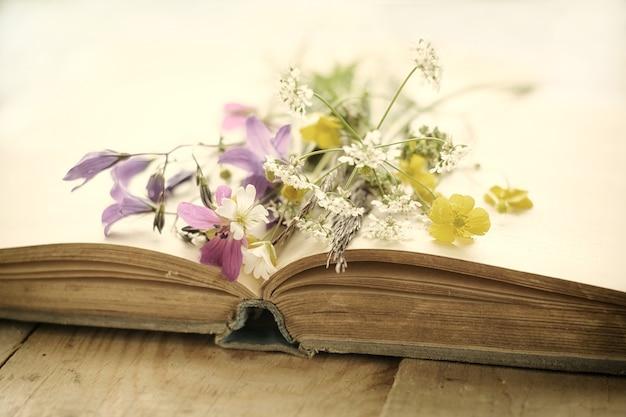 Livre vintage avec bouquet de fleurs de prairie fond vintage nostalgique