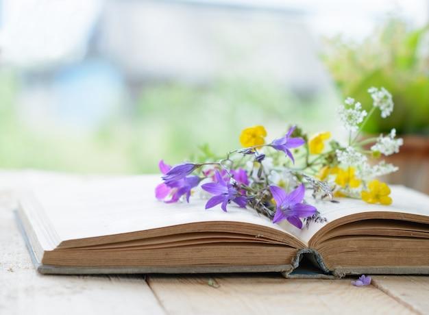 Livre vintage avec bouquet de fleurs sauvages, surface vintage nostalgique