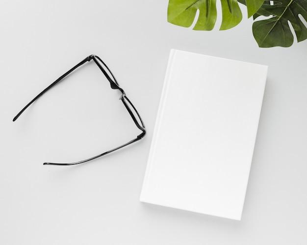 Livre de vue de dessus avec des lunettes et des feuilles à côté