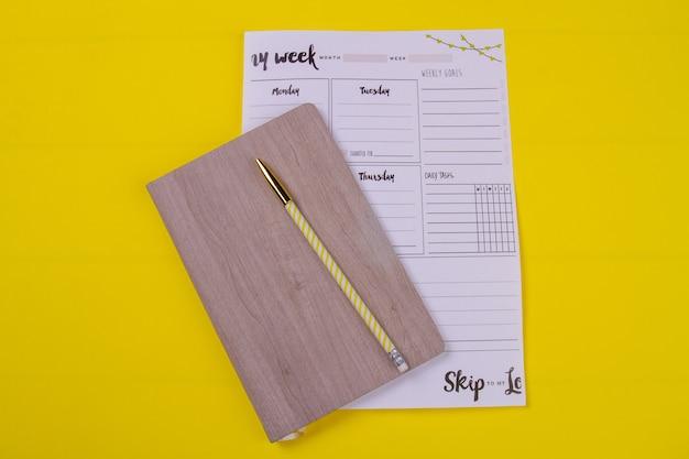 Livre vue de dessus avec stylo et calendrier hebdomadaire.