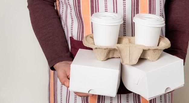 Livrer des boîtes en papier et des contenants à emporter avec deux tasses de café blanches.