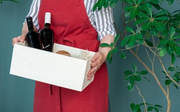 Livrer dans un tablier rouge contient des bouteilles de vin dans une boîte blanche avec noix de coco et avocat, concept de commande en ligne.