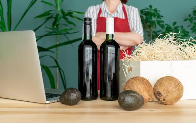 Livrer dans un tablier rouge met des bouteilles de vin dans une boîte blanche avec des noix de coco et de l'avocat, concept de commande en ligne.