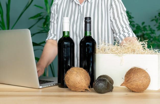 Livrer met des bouteilles de vin dans une boîte blanche avec des noix de coco et de l'avocat, concept de commande en ligne.