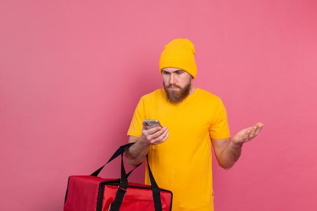 Livrer de la nourriture avec indignation mécontente en regardant le téléphone sur rose